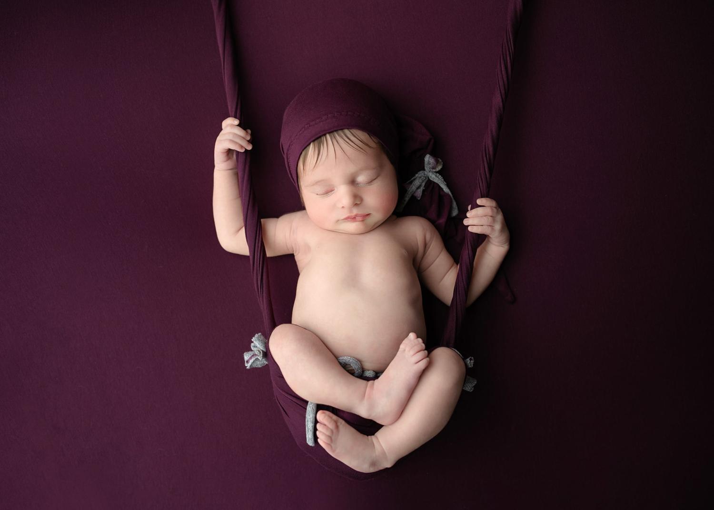 recién nacido en manta morada