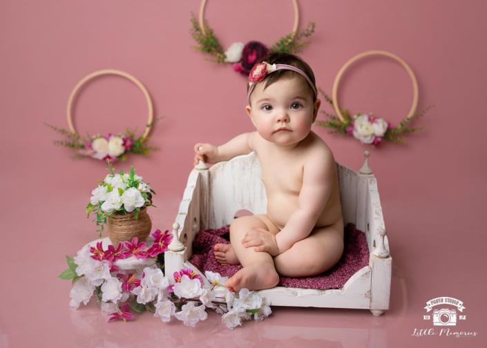 niña bebé sentada en banco blanco