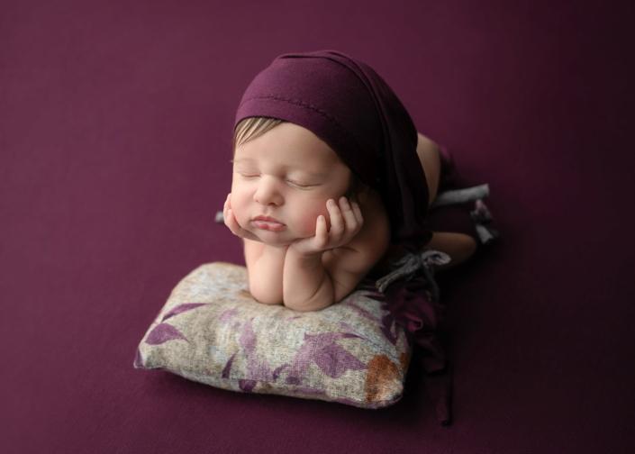 bebé dormido con gorro morado y cojín de flores