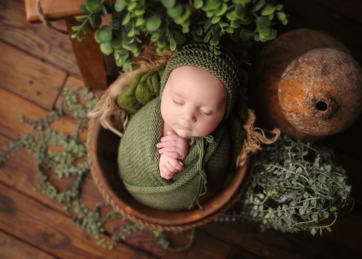 bebé en un cubo envuelto en manta verde