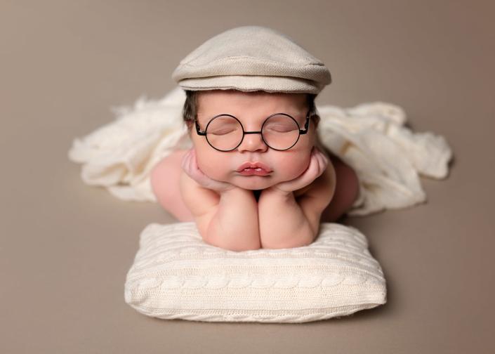 recién nacido con gafas y gorra